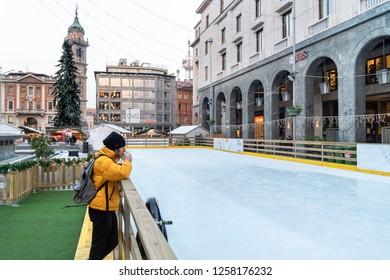 Varese, Italy - December 6, 2018: Woman is drinking coffee near the ice rink on the Monte Grappa square in the center of Varese at Christmas time, Italy