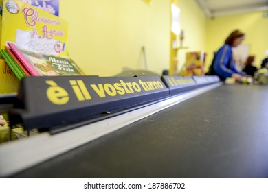 VARESE, ITALY-APRIL 11, 2014: Cashier working at the cash register in a supermarket, in Varese.