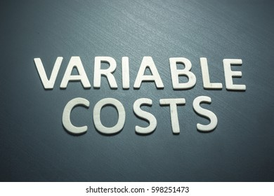 Variable costs written with wooden letters on a green background to understand a concept of economics and finance