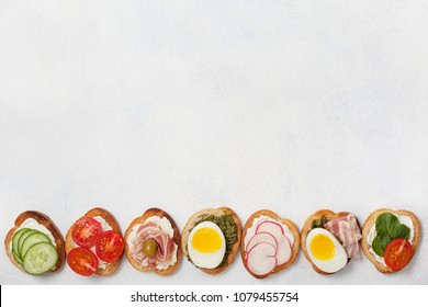 variants of sandwiches with cream cheese, pesto, tomatoes, cucumber, egg, bacon, radishes on a light background. view from above