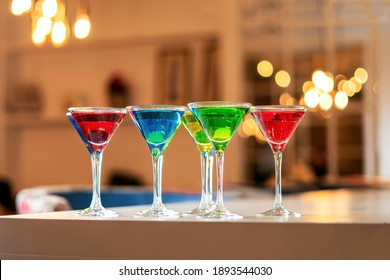 Variation alcoholic drinks served on bar counter. Colored drinks in glasses. Beautiful background, evening mood.
