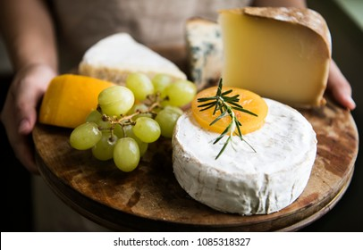 Variation of cheese and green grapes on a wooden platter food photography recipe idea