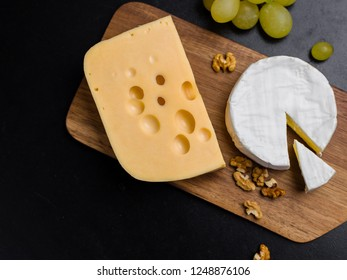 Variation of cheese, nuts and grapes on wooden cutting board. Camembert cheese and edam cheese. Food for wine and romantic, From top view.