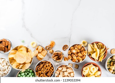 Variation different unhealthy snacks crackers, sweet salted popcorn, tortillas, nuts, straws, bretsels, white marble background copy space