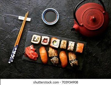 Variation of sushi and rolls on stone table. Sashimi set with chopsticks. Top view with copy space.