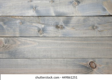Varicolored cheap knotted weathered wood texture as background.