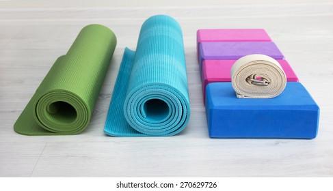 varicolored iyengar yoga props blocks, strap, roller and carpet