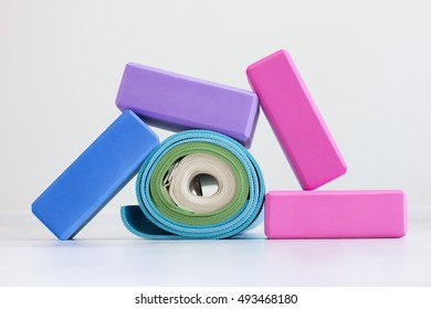 Varicolored iyengar yoga props. Blocks, strap and carpets