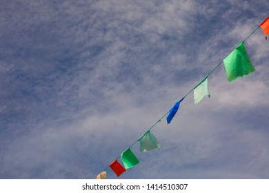 Varicolored pennants on a rope against clear blue sky; Bunting flags; Let's have a party
