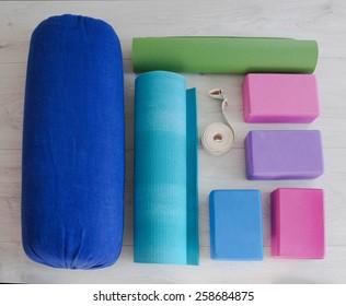 varicolored yoga props blocks, strap, roller and carpet
