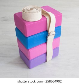 varicoloured yoga props blocks with  buttoned strap