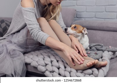Varicose veins prevention, woman wearing high Compression Stockings close up, dog supports owner