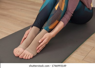 Varicose veins prevention. Woman wearing Compression Stockings during Sport Exercises