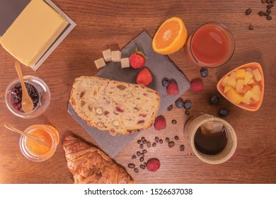 Varied breakfast with fresh fruit bread and cereals fresh orange juice honey and strawberry jam, butter tea and berries and fruit salad coffee beans and croissant