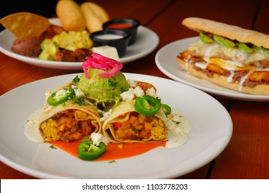 Varied breakfasts on a wooden table of a restaurant. Eggs, Salvadoran beans, bread and banana.