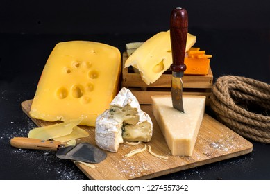 varied cheese on a black background on a wooden board with a knife