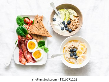 Varied sweet and savory breakfast - bacon with egg and vegetables, spinach salad, yogurt with granola and fruit, vegetarian oatmeal on a light background, top view