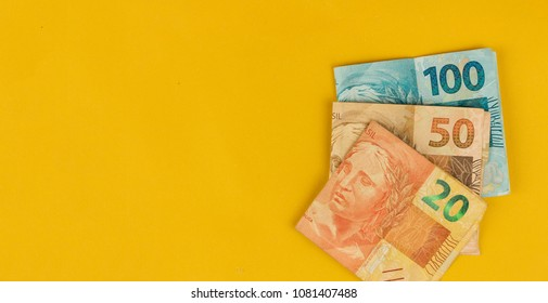 Varied values of Brazilian money isolared on yellow background