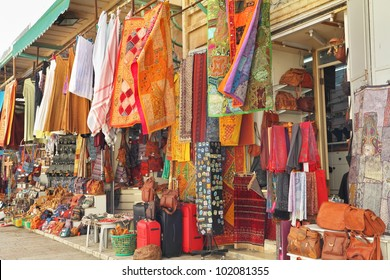 Variegated colors of oriental bazaar. The Arabian market in Jerusalem - bright motley fabrics and clothes are hung out for sale