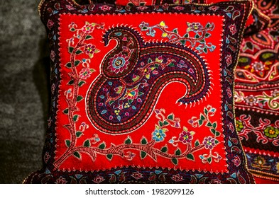 A variegated embroidered woolen pillow with oriental paisley patterns and twigs with flowers on a red background.