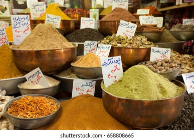 Varieties of colorful aromatic spice powders and dried herbs in traditional copper bowls in an old bazaar of Iran.