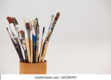 Varieties of paint brushes in jar against white background