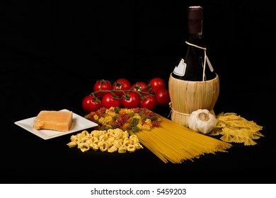 Varieties of pasta, tomatoes, garlic, cheese and wine on black background
