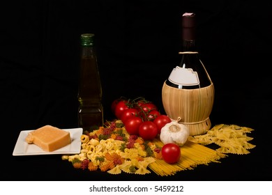 Varieties of pasta, tomatoes, garlic, cheese, olive oil and wine on black background
