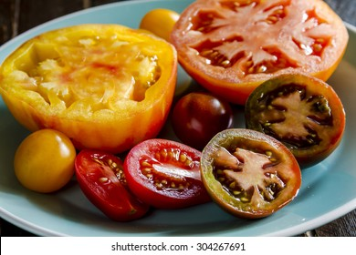 Varieties of sliced heirloom tomatoes sitting on light blue plate
