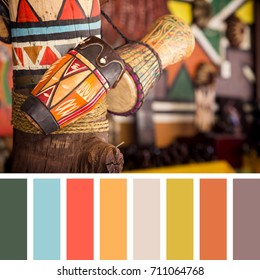 A variety of African drums for sale in a market, In a colour palette with complimentary colour swatches.