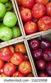 A variety of apples in a market, sorted in wooden bins.