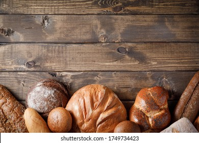 Variety of baked goods on wooden table background. Bakery concept - gold rustic crusty loaves of bread and buns. Still life captured from above (top view, flat lay), banner layout. Copy space