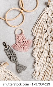 Variety of beautiful hand made macrame and accessories. Made of cotton threads using macrame technique. Can be used as home decor or key chain. Handmade macrame. Top view. Textured white surface.