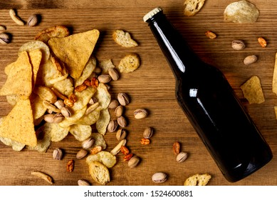 A variety of beer snacks and a bottle of dark beer on a wooden background, top view. Nachos, chips, pistachios, other snacks and beer on a wooden table in a bar, flat lay, mock-up