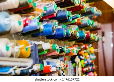 variety big and used spools of colorful sewing threads. Tailor shop theme background, Textiles and clothing industry concept. selective focus.Colorful thread spools used in fabric and textile industry