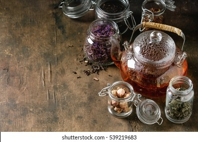 Variety of black, green and herbal dry tea leaves in glass jars with vintage strainer and teapot of hot tea over old dark wooden background. Close up, copy space