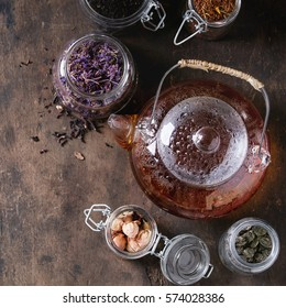 Variety of black, green and herbal dry tea leaves in glass jars with vintage strainer and teapot of hot tea over old dark wooden background. Top view with copy space. Square image
