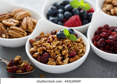 Variety of breakfast food with nuts and granola in small bowls