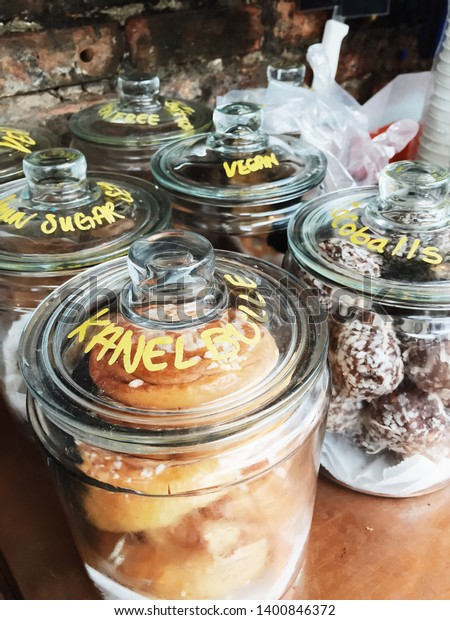 A variety of breakfast treats for sale in a coffee shop in glass canisters