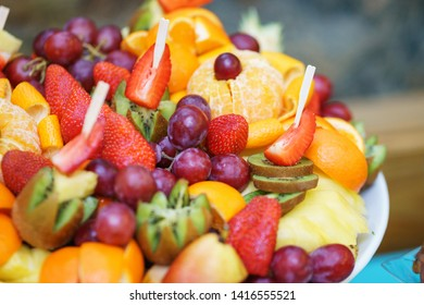 Variety of bright colored juicy fruits on a plate. Summer bright fruit plate table in the restaurant. Catering and meals for guests during the holiday and events. Soft focus and beautiful bokeh.