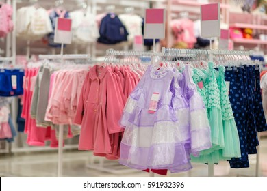 Variety of bright girl dresses on hangers in kids clothes store