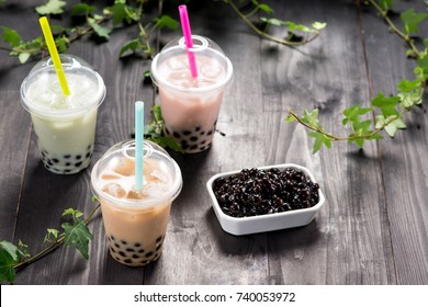 Variety of bubble tea in plastic cups with straws on a wooden table.