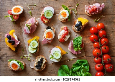 Variety of canape with hummus, ham and cheese, eggs and fresh vegetables on wooden table. Top view of healthy snack concept.