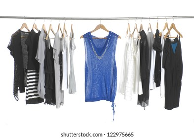 Variety of casual fashion clothing on hangers and shoes