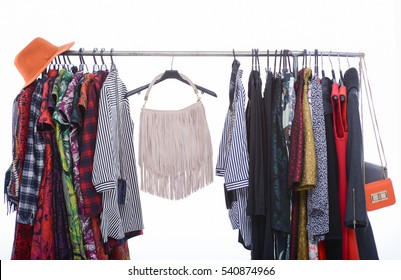 Variety of casual female clothing with bag, hat hanging on hangers