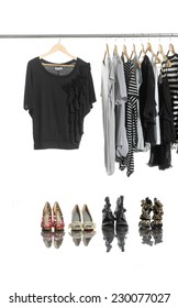 Variety of casual female clothing on hangers and shoes