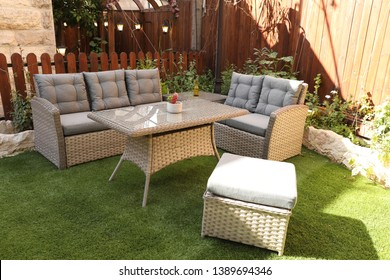 A variety of chairs, tables, rattan sofas, plastic and wood, in an old green garden with different angles