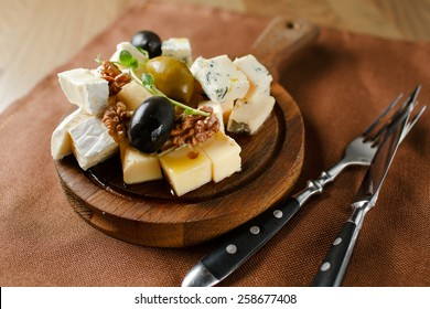 Variety of cheese with nuts and olives laid out on a wooden board. Food background with Wine