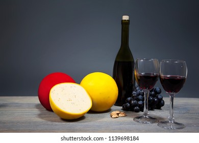 Variety cheese with red wine and a bunch of grapes. Composition from gastronomic products isolated on gray background