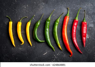 Variety of chili peppers. Red, green and yellow chili pepper on dark background top view